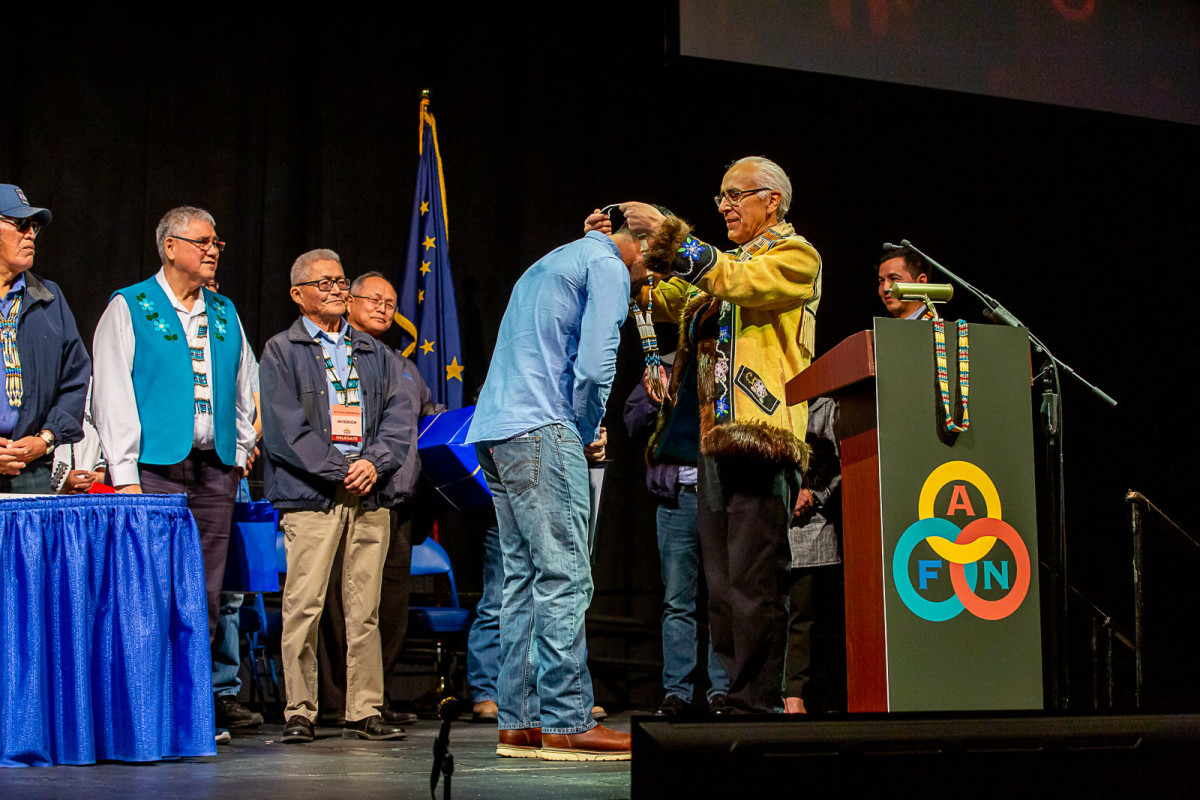 Alaska Federation of Natives co-chairman Will Mayo presents Pete Kaiser with a chief's necklace, Oct. 14. (Courtesy Kaiser Racing Kennel)