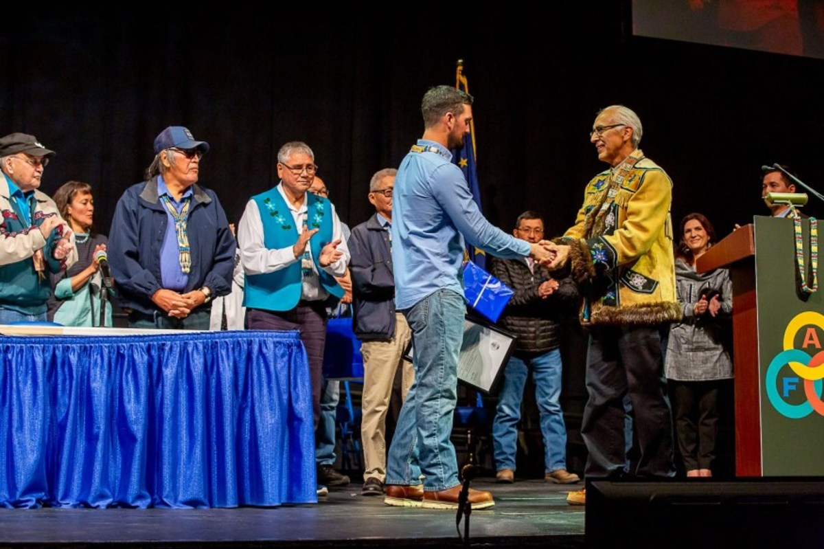 Alaska Federation of Natives co-chairman Will Mayo congratulates Pete Kaiser Oct. 14 at the AFN convention. Kaiser was the keynote speaker. (Courtesy Kaiser Racing Kennel)