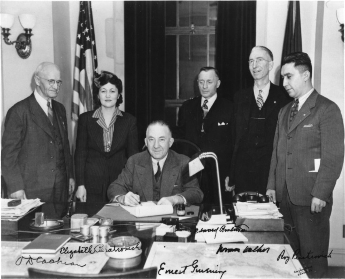 Alaska Governor Ernest Gruening (seated) signs the Anti-Discrimination Act of 1945. Witnessing are (left to right): O.D. Cochran, Elizabeth Peratrovich (president of the Alaska Native Sisterhood), Edward Anderson, Norman Walker, and Roy Peratrovich. (Photo Courtesy Alaska State Library, Alaska Territorial Governors Photograph Collection)