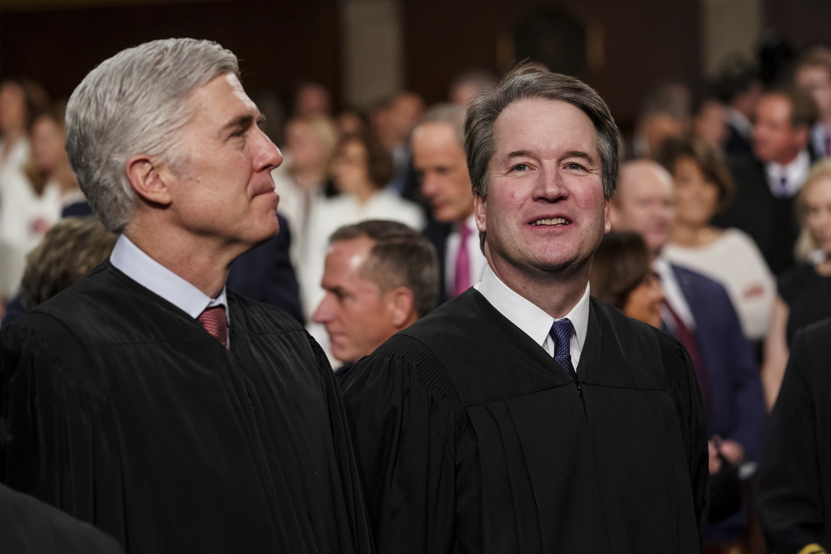 """In this Feb. 5, 2019 file photo, Supreme Court Associate Justices Neil Gorsuch, left, and Brett Kavanaugh watch as President Donald Trump arrives to give his State of the Union address to a joint session on Congress at the Capitol in Washington. President Donald Trump's two Supreme Court appointees are on opposite sides of two of three cases the justices decided Tuesday March 19. Justice Neil Gorsuch is joining the court's liberal justices in ruling that a Washington state Indian tribe doesn't have to pay a state fuel tax. Gorsuch says an 1855 treaty makes a """"handful of modest promises"""" to the Yakama Nation, including the right to move goods to market freely. Justice Brett Kavanaugh is dissenting, arguing that the treaty merely gives tribal members the same right to travel as everyone else. (Doug Mills/The New York Times via AP, Pool)"""