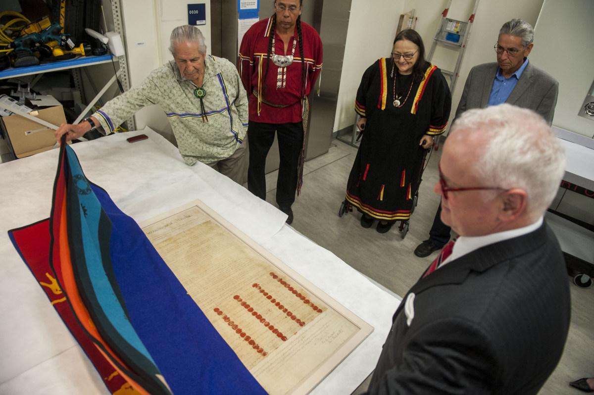 """IMAGE DISTRIBUTED FOR THE SMITHSONIAN'S NATIONAL MUSEUM OF THE AMERICAN INDIAN - From left, Faithkeeper of the Turtle Clan of the Onondaga Nation of the Haudenosaunee Confederacy Oren Lyons, PhD, The Tadodaho of the Haudenosaunee Confederacy Chief Sidney Hill, Guest Curator Suzan Harjo (Cheyenne and Hodulgee Muscogee), National Museum of the American Indian Director Kevin Gover (Pawnee) and Executive for Legislative Archives, Presidential Libraries Jim Gardner, front right, unveil the Treaty of Canandaigua of 1794 on loan from the National Archives in the Smithsonian's National Museum of the American Indian on Monday, Sept. 8, 2014 in Washington. The Treaty, between the Haudenosaunee Confederacy and the United States, is signed by President George Washington and The Six Nations (Iroquois). The exhibition, """"Nation to Nation: Treaties Between the United States and American Indian Nations,"""" opens Sept. 21, 2014, at the Smithsonian's National Museum of the American Indian in Washington. AmericanIndian.si.edu. (Kevin Wolf/AP Images for The Smithsonian's National Museum of the American Indian)"""