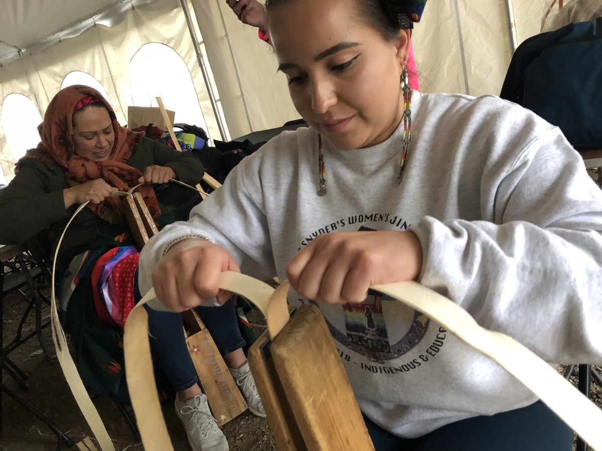 Shaina Snyder (foreground) attends an elm bark basket making that was moved into the main dining tent due to the weather Saturday evening. (Photo by C.A. Printup)