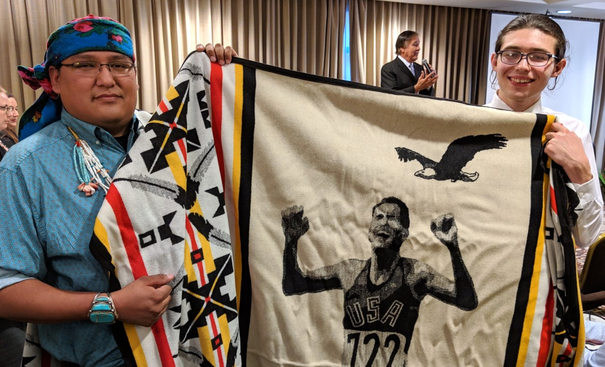 Photo: Native youth Dreamstarters Carl Petersen, Cheyenne River Sioux and Kevin Belin, Navajo hold up a prized Pendleton blanket honoring Billy Mills. Mills was speaking in the background and thanking the crowd for honoring Native youth. (Photo: Vincent Schilling)