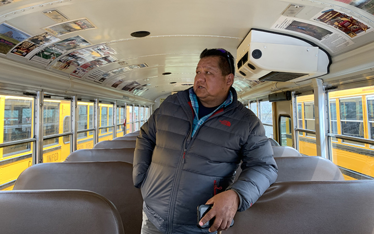 """Freddie Yazzie puts pictures of local legends in his school bus, which he calls the Legacy of Excellence. """"When I think about it, I'm part of their education,"""" Yazzie said. (Photo by Jake Goodrick/Cronkite News)"""