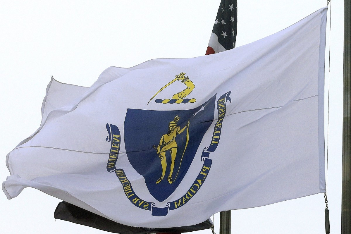 In this Monday, May 2, 2016 file photo, the Massachusetts state flag flies in front of Boston City Hall. Native American groups in the state are rallying in front of the State House in Boston on Thursday, July 16, 2020, to urge passage of legislation banning the use of Indian mascots and creating a commission to review the state's seal and motto. (AP Photo/Steven Senne, File)