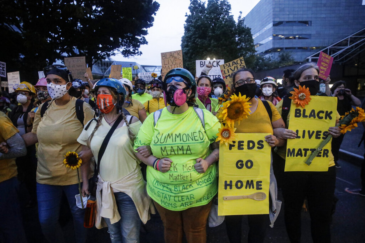 """Members of the """"Wall of Moms"""" march during a Black Lives Matter protest at the Mark O. Hatfield United States Courthouse Thursday, July 23, 2020, in Portland, Ore. (AP Photo/Marcio Jose Sanchez)"""