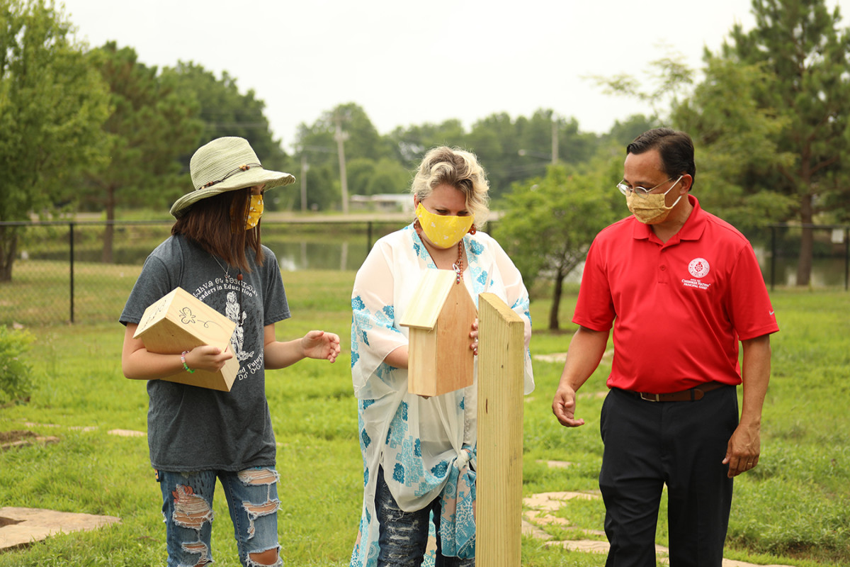 Pictured: Cherokee Nation's First Family, Principal Chief Chuck Hoskin Jr., First Lady January Hoskin and First Daughter Jasmine Hoskin place bee pollinator homes at the tribe's Heirloom Garden in Tahlequah. The pollinator homes are part of the First Lady's initiative to help better the environment as well as to help provide a safe habitat for bees and other pollinators.