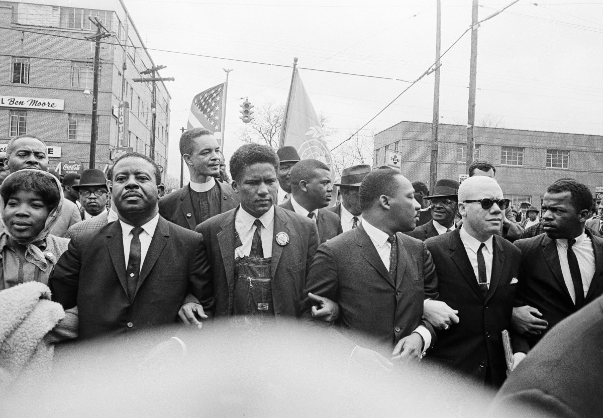 FILE - In this March 17, 1965, file photo, Dr. Martin Luther King Jr., fourth from left, foreground, locks arms with his aides as he leads a march of several thousands to the courthouse in Montgomery, Ala. From left are: an unidentified woman, Rev. Ralph Abernathy, James Foreman, King, Jesse Douglas Sr., and John Lewis. Lewis, who carried the struggle against racial discrimination from Southern battlegrounds of the 1960s to the halls of Congress, died Friday, July 17, 2020. (AP Photo/File)