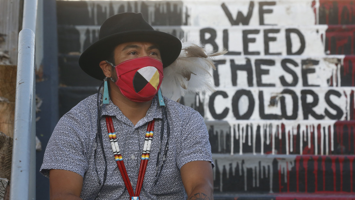 """Native American advocate Carl Moore sits near the phrase """"We Bleed These Colors"""" along a walkway which leads from the Bountiful High School parking lot up to the football field Tuesday, July 28, 2020, in Bountiful, Utah. While advocates have made strides in getting Native American symbols and names changed in sports, they say there's still work to do mainly at the high school level, where mascots like Braves, Indians, Warriors, Chiefs and Redskins persist. (AP Photo/Rick Bowmer)"""