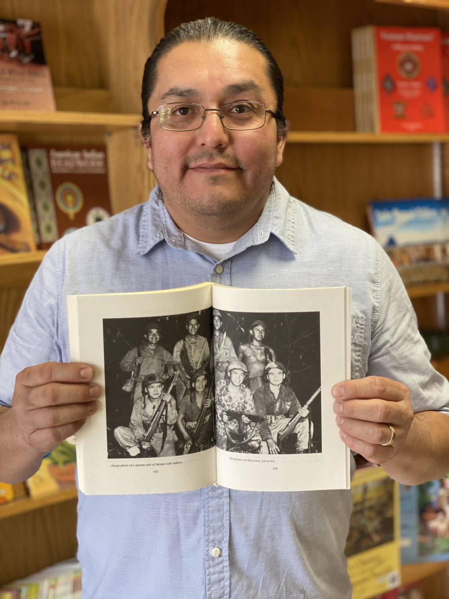 LT Goodluck holds a book with a photo of his grandfather, John V. Goodluck, and other Navajo Code Talkers (Photo courtesy of LT Goodluck)