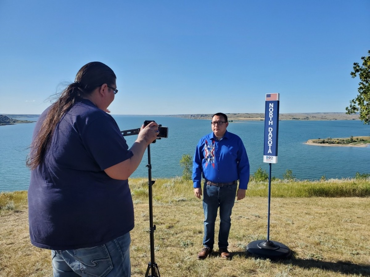 Cesar Alvarez, MHA Nation, films his DNC roll call remarks from the Fort Berthold Reservation in North Dakota. Also pictured is Jaron Noisy Hawk. (Photo by Roger White Owl)