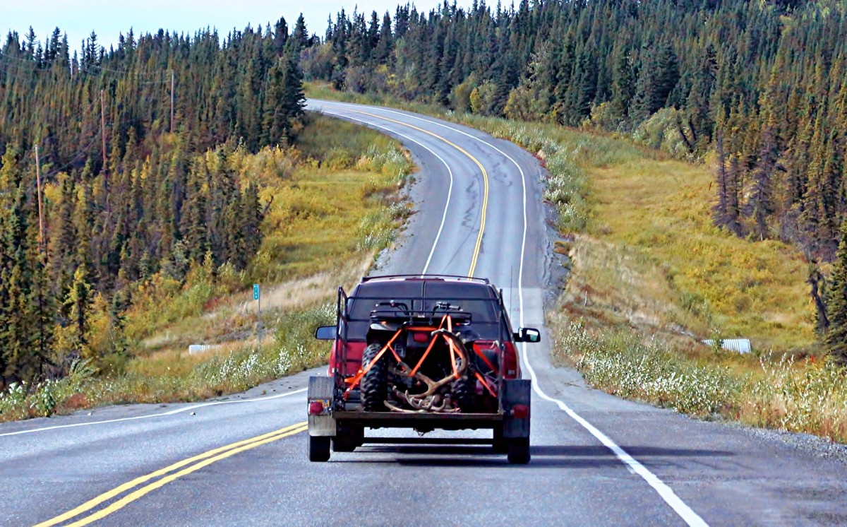 """A hunter on the road to the Anchorage area from eastern Interior Alaska carrying an all-terrain vehicle and caribou antlers. The photographer commented, """"Returning to our cabin, we came upon this successful hunter with a beautiful caribou rack in the bed of his truck. I sure hope he packed out the meat as well - or at least donated it to a needy family."""" (Photo by JLS Photography, courtesy of Creative Commons)"""