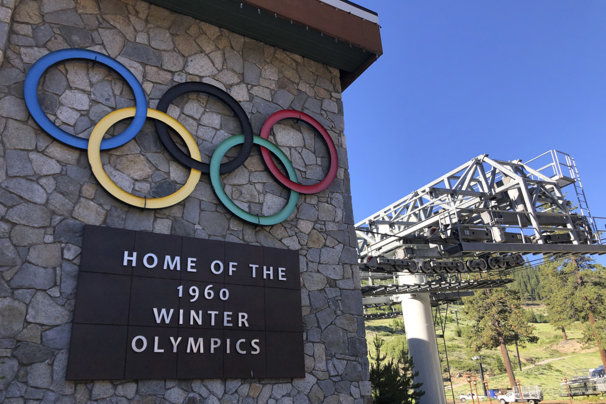 """A sign marking the 1960 Winter Olympics is seen by a chairlift at Squaw Valley Ski Resort in Olympic Valley, Calif., July 9, 2020. California's Squaw Valley Ski Resort is considering changing its name to remove """"squaw,"""" a derogatory term for Native American women. Squaw Valley President & CEO Ron Cohen says resort officials are meeting with shareholders and the local Washoe tribal leadership to get their input. He says he can't give a timeline on when the decision will be made. The renaming of Squaw Valley Ski Resort is one of many efforts across the nation to address colonialism and indigenous oppression. (AP Photo/Haven Daley)"""