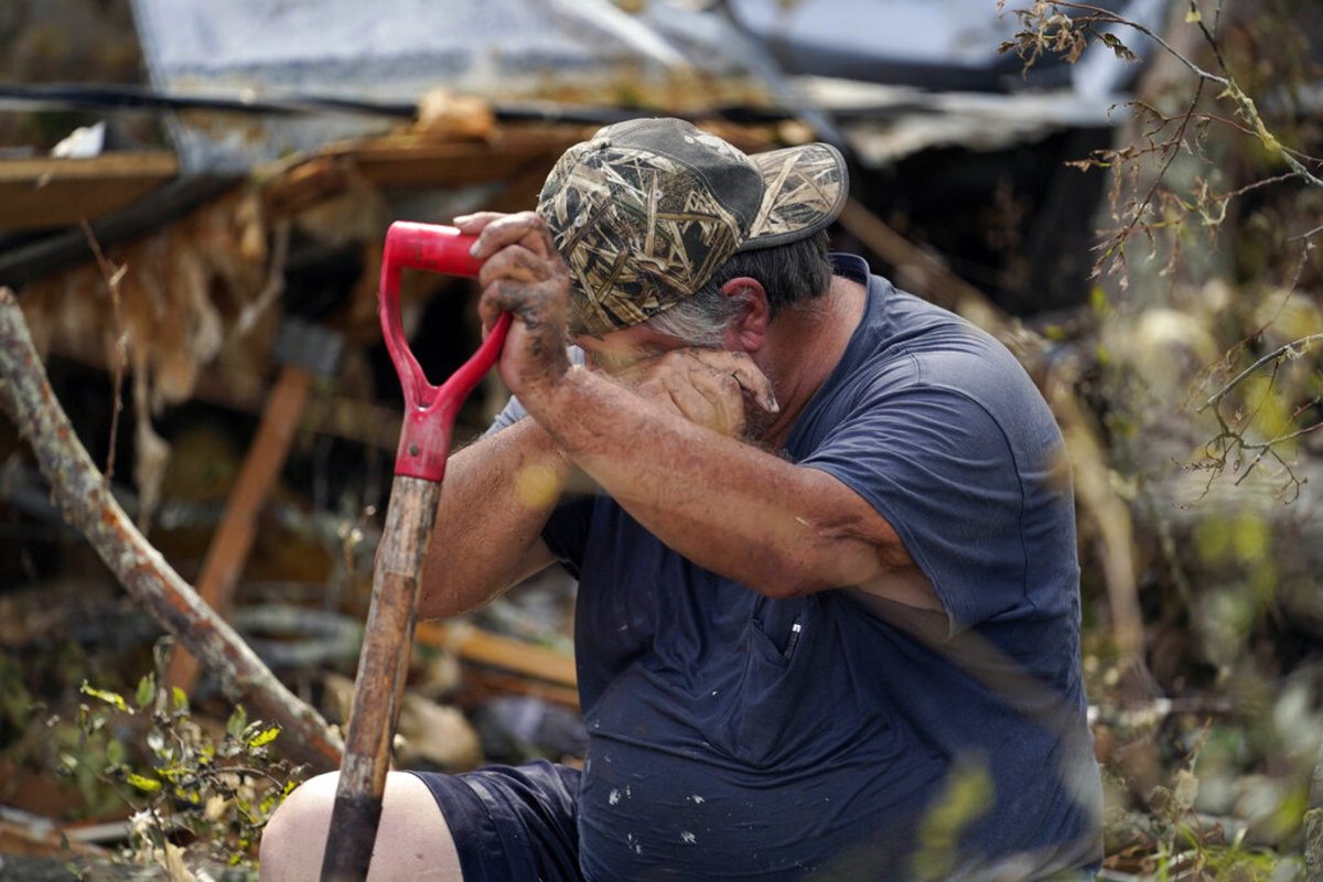 """Bradley Beard wipes his face as he rests while he searches in vain for his water shutoff valve, next to his heavily damaged home and the destroyed trailer home of his daughter Nicole in Hackberry, La., in the aftermath of Hurricane Laura, Saturday, Aug. 29, 2020. """"This is too much for a 62 year old man,"""" he said."""" (AP Photo/Gerald Herbert)"""