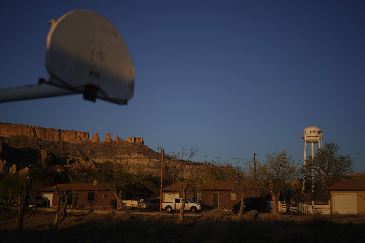 In this Sunday, April 19, 2020, the water tower and a basketball backboard at the school in Chilchinbeto, Arizona, on the Navajo reservation, are seen at sunrise. (AP Photo/Carolyn Kaster, File)