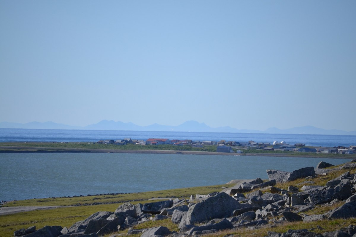 The village of Gambell, Alaska in the summer, with Troutman Lake in the foreground and the mountains of Chukotka, Russia in the background. (Photo by Lana Schwartz, courtesy of Wikimedia)