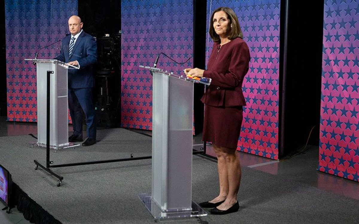 Democrat Mark Kelly and Republican Sen. Martha McSally are separated by plexiglass as they participate in a debate at the Walter Cronkite School of Journalism and Mass Communication. (Photo by Rob Schumacher/POOL/The Arizona Republic via USA TODAY NETWORK)