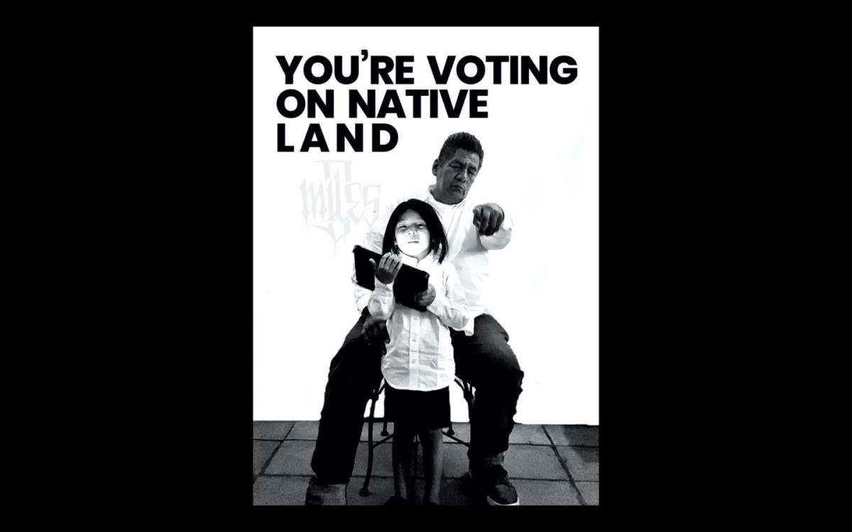 """Apache artist Douglas Miles created a social campaign and """"You're Voting on Native Land"""" mural that is displayed on his homelands at the San Carlos Apache Reservation in Arizona. (Photo courtesy of Katie Dunham)"""