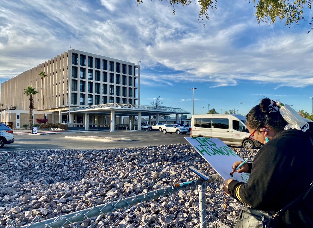 Nalene Gene works finishes up her sign to protest the closing of Phoenix Indian Medical Center's birthing center. About a dozen people protested the closing on Thursday, Nov. 19, 2020. (Photo by Dalton Walker, Indian Country Today)