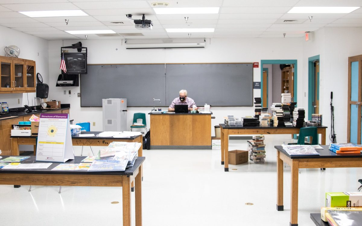 Piñon High School science teacher James Gustafson teaches virtually from his empty classroom. Unlike their students, the school's teachers report to campus each day, careful to wear masks and keep space between them. (Photo by Megan Marples/Cronkite News)