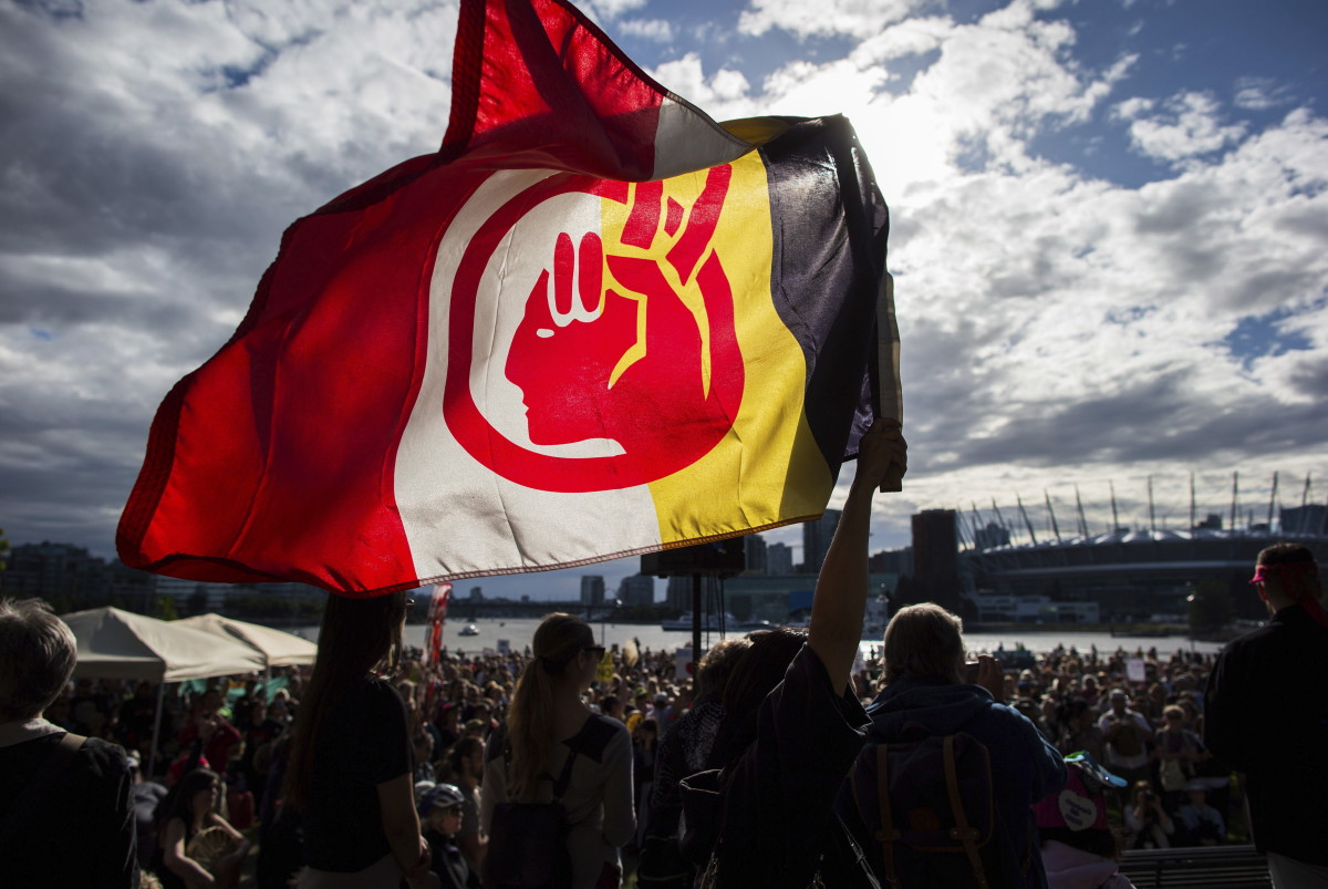 A woman silhouetted holds a flag of the American Indian Movement during a protest against the Kinder Morgan's Trans Mountain pipeline expansion, in Vancouver, British Columbia, Tuesday, May 29, 2018. Canada's federal government said Tuesday it is buying the controversial pipeline from the Alberta oil sands to the Pacific Coast to ensure it gets built. (Darryl Dyck/The Canadian Press via AP)