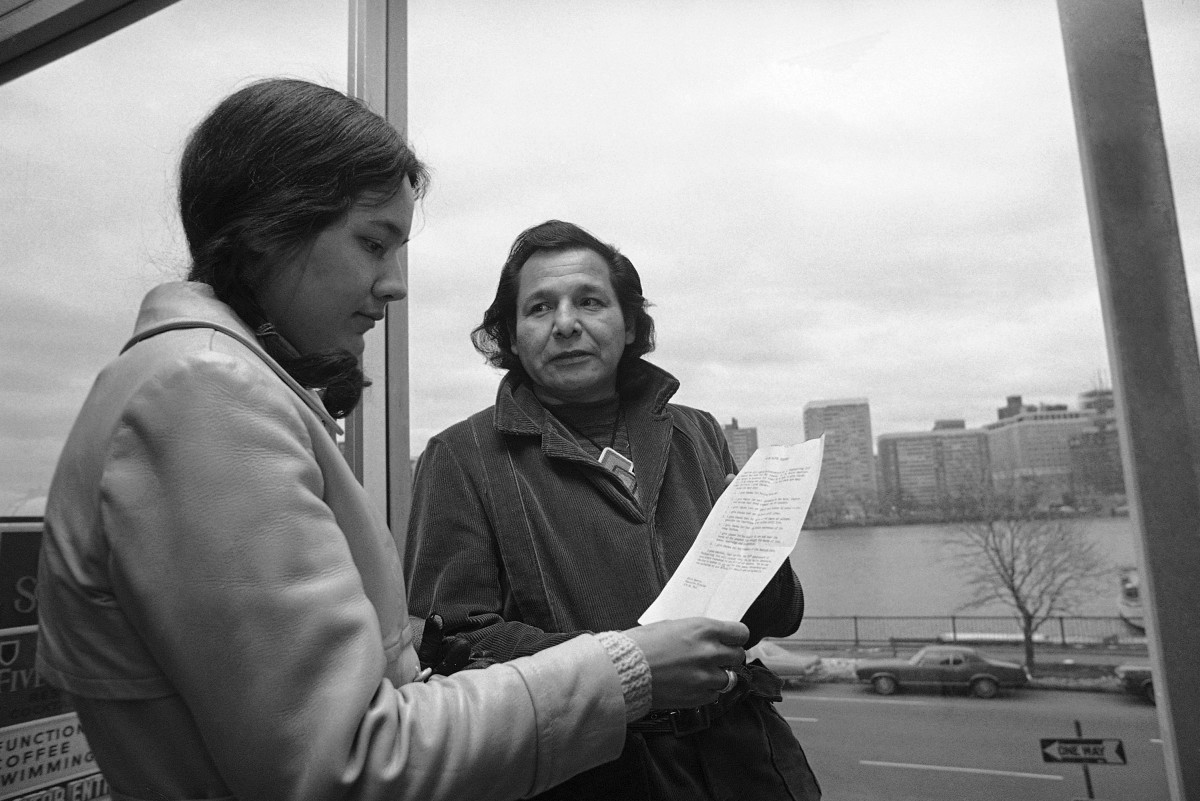 In this Nov. 4, 1971 file photo, Eddie Benton, a holy man of the Chippewa Indian Tribe, shows a prayer he wrote to Linda Jeffers, of Vineyard Haven, Martha's Vineyard, Mass., a member of the Wampanoag Tribe in Cambridge, Mass. Eddie Benton-Banai, one of the founders of the American Indian Movement that was formed partly in response to alleged police brutality against Indigenous people, has died. He was 89. A family friend says Benton-Banai died Monday, Nov. 30, 2020 at a care center in Hayward, Wis., where he had been staying for months. (AP Photo/J. Walter Green, File)