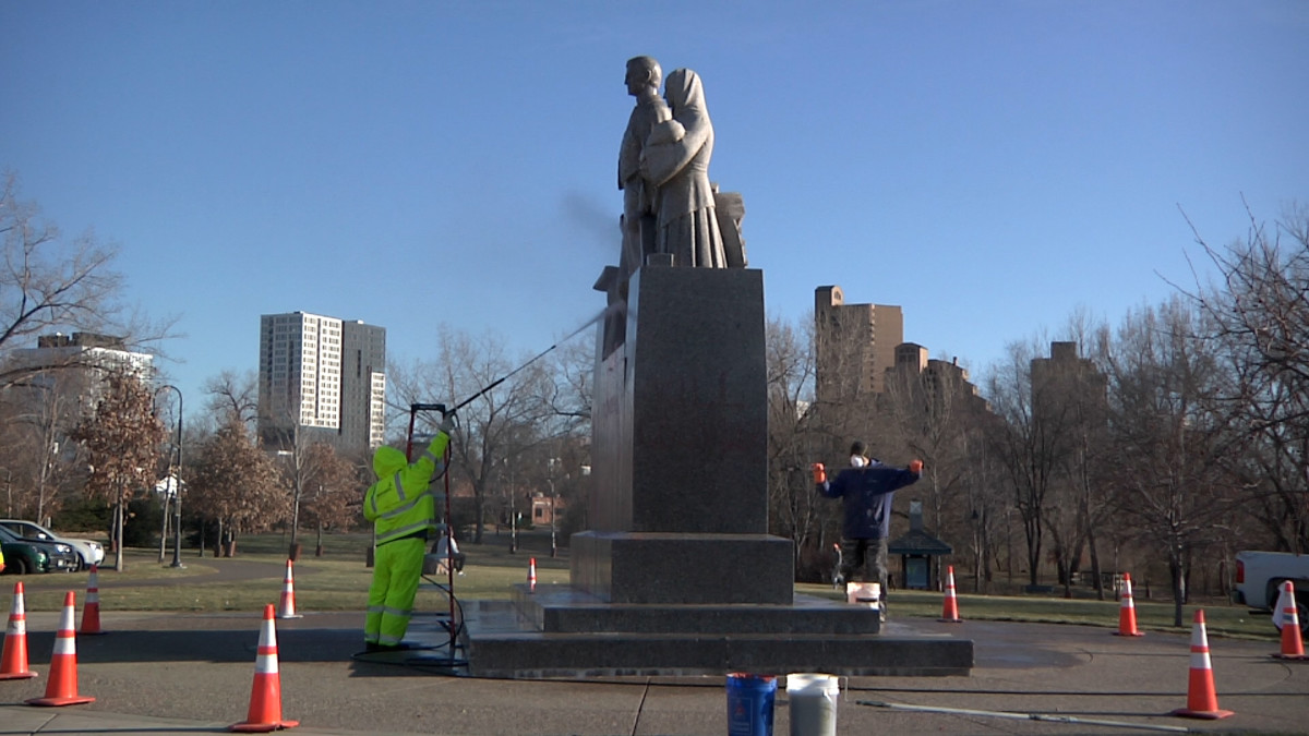 """City crews reacted swiftly the day after a statue to pioneer settlers was hit with protest graffiti on Thanksgiving 2020. American Indian Movement leaders lauded the activists. """"It's about time that we take something back or take something down from this colonial government,"""" said Frank Paro, Grand Portage Chippewa, the day after the actions. """"Whoever is responsible for this well I'll take my hat off to them and say 'Miigwetch,' 'thank you.' I'd like to have been there."""" (Photo by Stewart Huntington)"""
