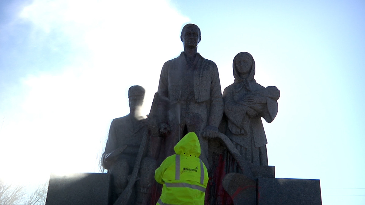 Minneapolis city crews power-wash a statue of a pioneer settler family after activists targeted the monument with anti-colonial messages on Thanksgiving 2020. No arrests have been made in connection with the protest action. (Photo by Stewart Huntington)