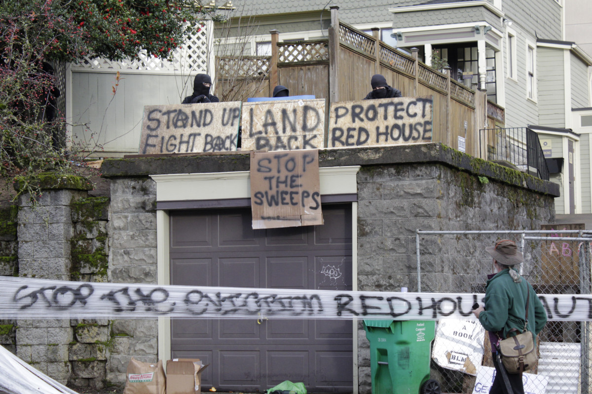 """This Dec. 8, 2020 photo shows a home on North Mississippi Avenue in Portland, Ore. where protesters have camped to prevent a Black and Indigenous family from being forced to leave the foreclosed home, which has been dubbed the """"Red House on Mississippi"""". (Beth Nakamura/The Oregonian via AP)"""