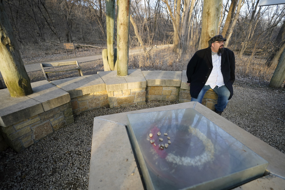 Rev. Jim Bear Jacobs stands at Fort Snelling State Park, Tuesday, Dec. 8, 2020, near Minneapolis, next to wooden markers bearing names of Native Americans who were part of some 1,600 Dakota people who were imprisoned in the aftermath of the 1862 U.S. - Dakota Conflict. Jacobs belongs to a Wisconsin-based Mohican tribe but was born in Minnesota and is well-versed in the grim chapters of its history regarding Native Americans. It is one of the historic sites in the Twin Cities area where he take social-justice groups on tours. (AP Photo/Jim Mone)