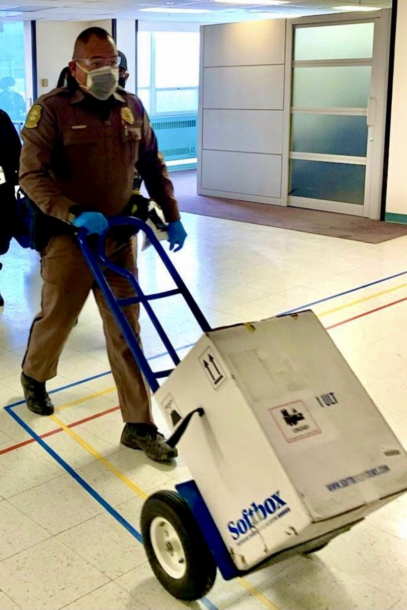 Navajo Nation Police Officer Jershon Begay transports the first delivery of COVID-19 vaccines to an ultra-cold freezer at the Indian Health Service's Gallup Indian Medical Center in Gallup, New Mexico, Dec. 14, 2020. (Photo courtesy of Indian Health Service)