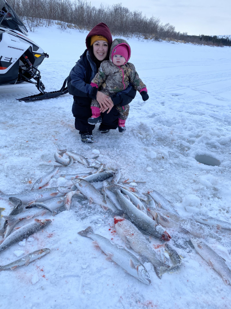 Inupiaq mother Kelsi Ivanoff and daughter Harlow Ralphie, with Dolly Varden trout, whitefish and grayling caught ice fishing in the Unalakleet River a few miles upriver from Unalakleet, Alaska. (Photo courtesy of Steve Ivanoff)