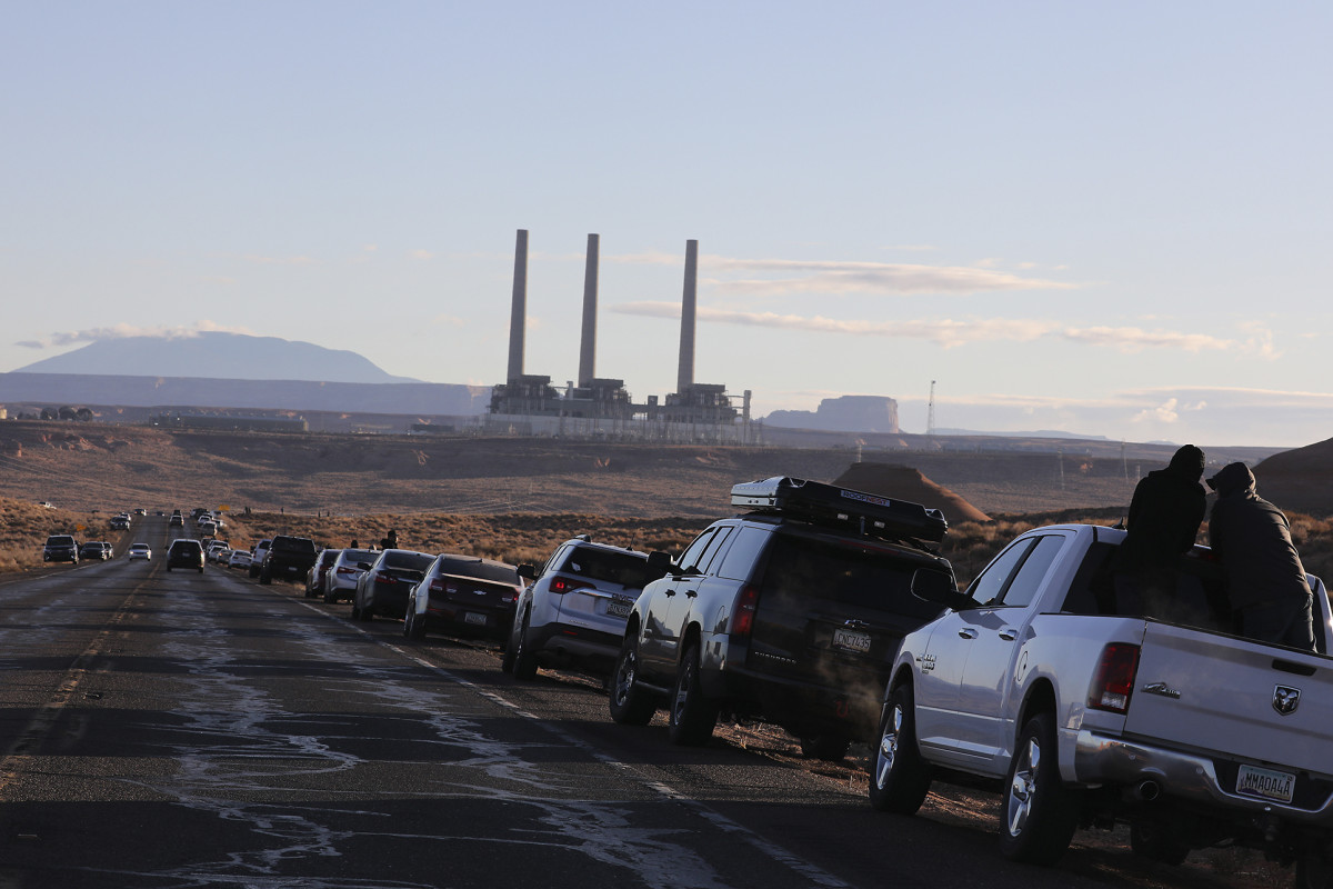 Cars lined Highway 98 in Page, Ariz., as spectators waited for the controlled collapse of the three chimneys at the Navajo Generating Station on Friday, Dec. 18, 2020. The 775-foot (236-meter) structures loomed over the Navajo Generating Station, a 2,250 megawatt plant that closed last year as natural gas became a cheaper alternative for electricity. (Jake Bacon/Arizona Daily Sun via AP)