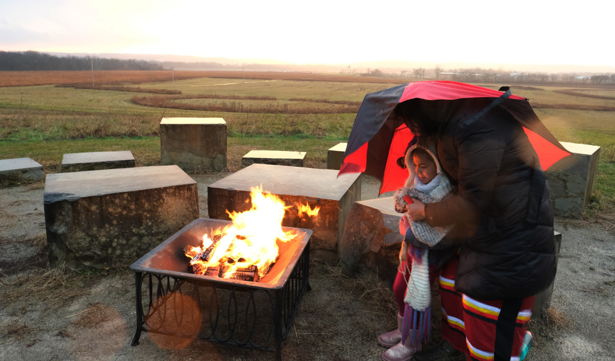 Shelly Corbin and her daughter Maelyn, 6 warm themselves by the fire as they await sunset at Hopeton Earthworks on the Winter Solstice. (Photo by Mary Annette Pember)