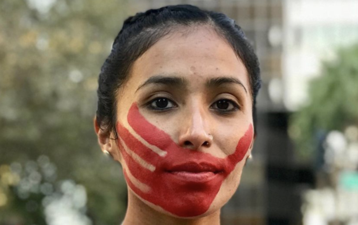 """The red handprint that Jordan Daniel wears across her face represents a message that Missing and Murdered Indigenous Women Movement wants out: """"We will not be silenced."""" (Photo courtesy Devin Whetstone)"""