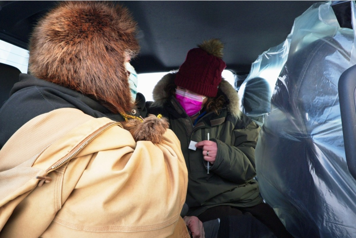 A villager receives a COVID-19 vaccination in a van on the tarmac in western Alaska. (Photo courtesy of Yukon-Kuskokwim Health Consortium, Alaska Native Tribal Health Consortium, State of Alaska.)