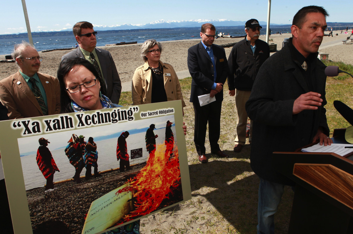 Regional leaders against coal exports hold a news conference Monday, April 22, 2013, at Golden Gardens Park in Seattle. At left, Patti Gobin of Tulalip Tribes holds a sign while Lummi Nation Councilmember Jay Julius, right, speaks. Others attending, in background, from left: Shoreline Deputy Mayor Chris Eggen; Shoreline Mayor Keith McGlashan; Sumner Councilmember Nancy M. Dumas; Edmonds Councilmember Strom Peterson; and Tulalip Tribes Chairman Melvin Sheldon, Jr. (AP Photo/Ken Lambert, The Seattle Times)