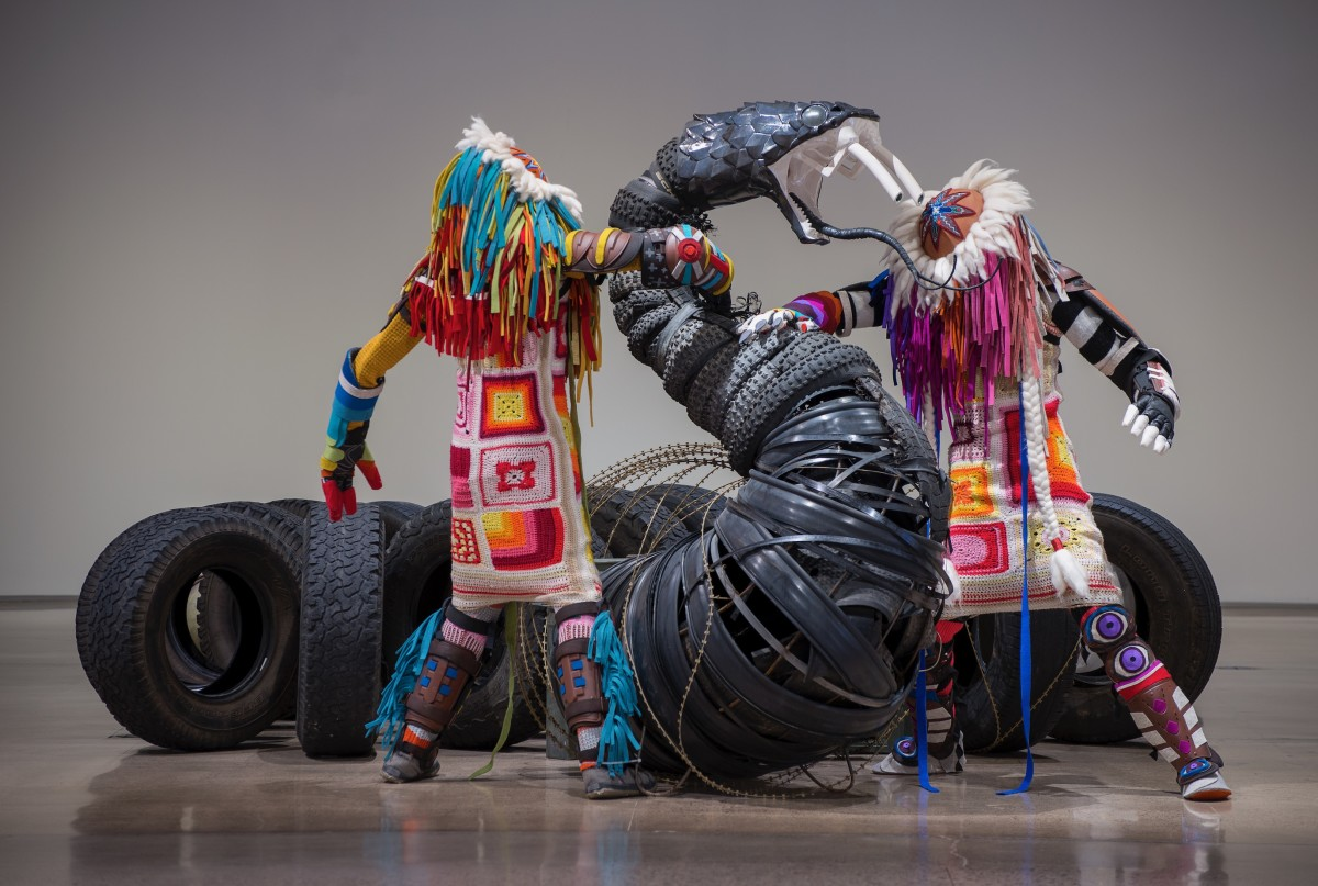 Cannupa Hanska Luger This Is Not A Snake / The One Who Checks & The One Who Balances, 2017-2020. Ceramic, riot gear, fiber, steel, oil drums, concertina wire, ammunition cans, trash, found objects, beadwork, surplus industrial felt, afghan, dimensions: 6.5 × 3 × 50 feet. An installation in a white walled museum. Two bright colored life-size humanoid figures with ceramic faced regalia engage with a massive ceramic headed snake form whose body is created by detritus of industry. Photo by Craig Smith; courtesy of Heard Museum.