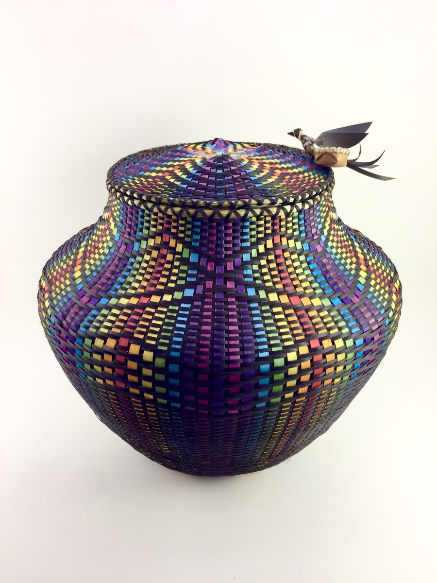 By Geo Soctomah Neptune, Passamaquoddy, a brightly colored basket, with rainbow stripes woven through intricate patterns of black strips. A tiny woven bird rests on one edge of the basket lid. (Photo courtesy of the artist)