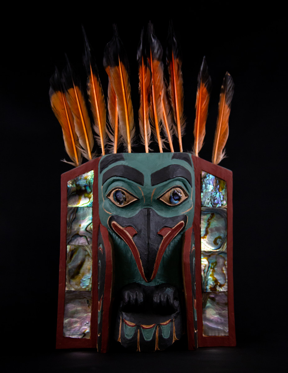 By Nathan Jackson, Raven Frontlet, 2020. Red alder, exterior house paint, flicker feathers, abalone inlay, dimensions 10 × 6 inches. (Photo by Stacey Williams.)