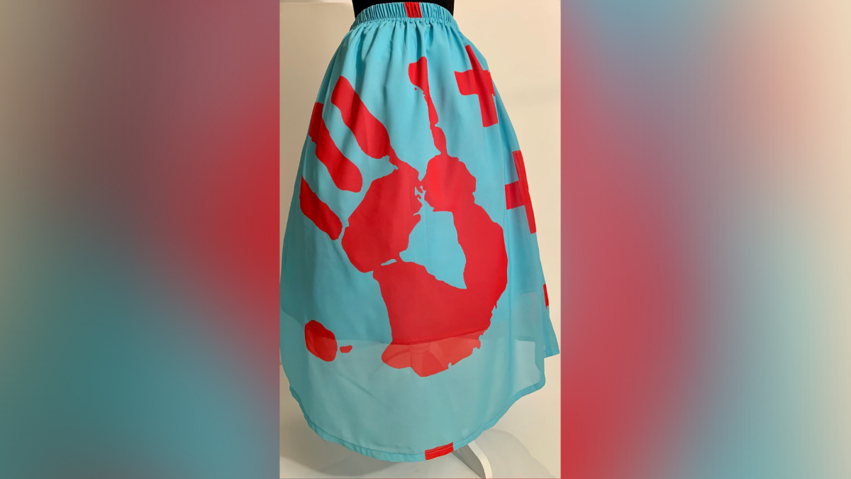 Turquoise skirt with red hand print and crosses, Cerruti Chiffon, inner layer is Poly French Crêpe. From Sky Eagle Collective. (Photo courtesy of designer Dante Biss-Grayson)