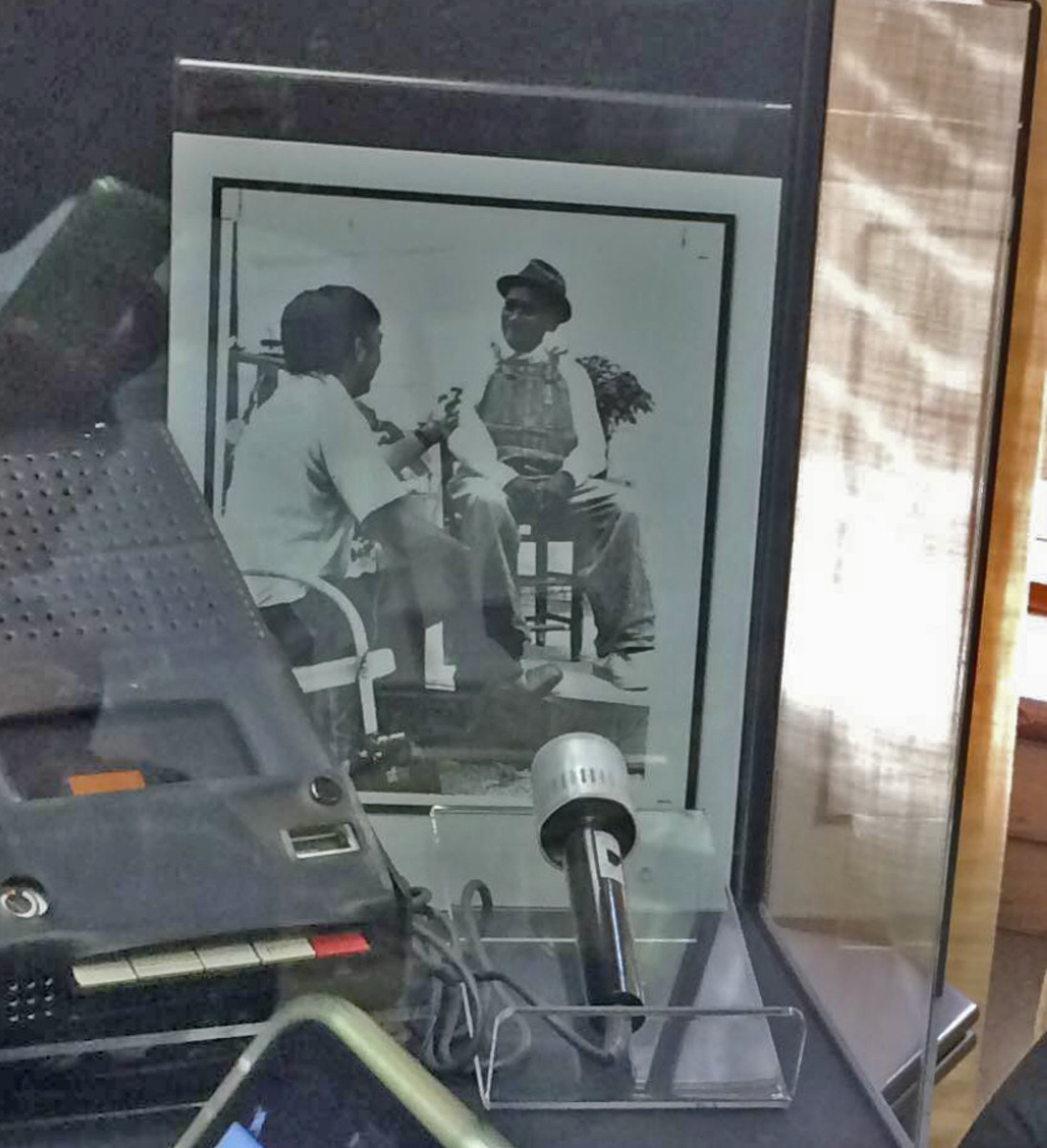 Dr. Anthony Paredes, the University of Florida's principal interviewer for the Porach Band of Creek Indians in Atmore, Alabama, which was one of the Tribes included in the original collection, interviewing one of the Creek Indian participants. The display case shows the actual microphone and tape recorder used in the photo. (Photo courtesy of the University of Florida)