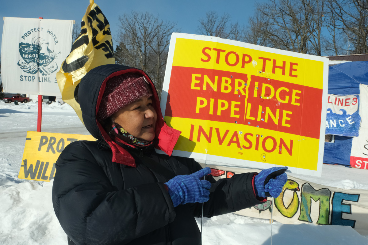 Tania Aubid of the Milles Band of Ojibwe, holds a bullet-riddled sign opposing the Enbridge Line 3 project in February 2021. The sign had been in front of her home. (Photo by Mary Annette Pember, Indian Country Today)