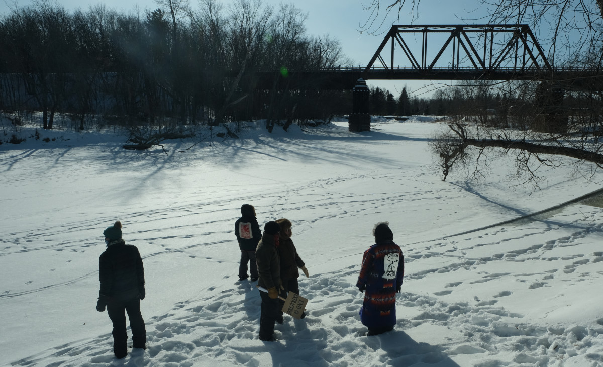 Water protectors pray along the Mississippi River in Palisade, MN. (Photo by Mary Annette Pember, Indian Country Today)