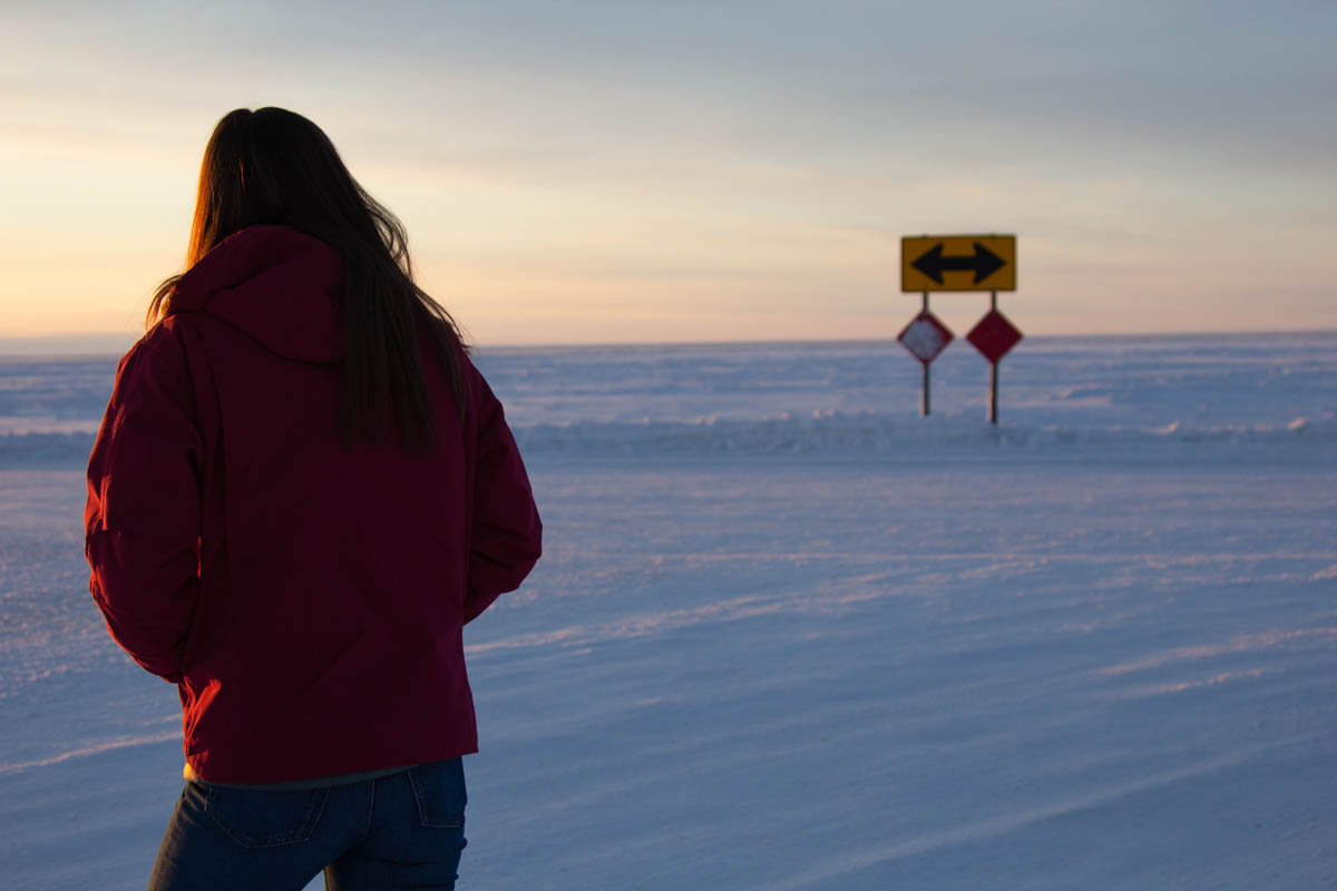 A woman in Nome at a crossroads with the ocean in the distance. (Photo by Brisa Alarcon, KNOM)
