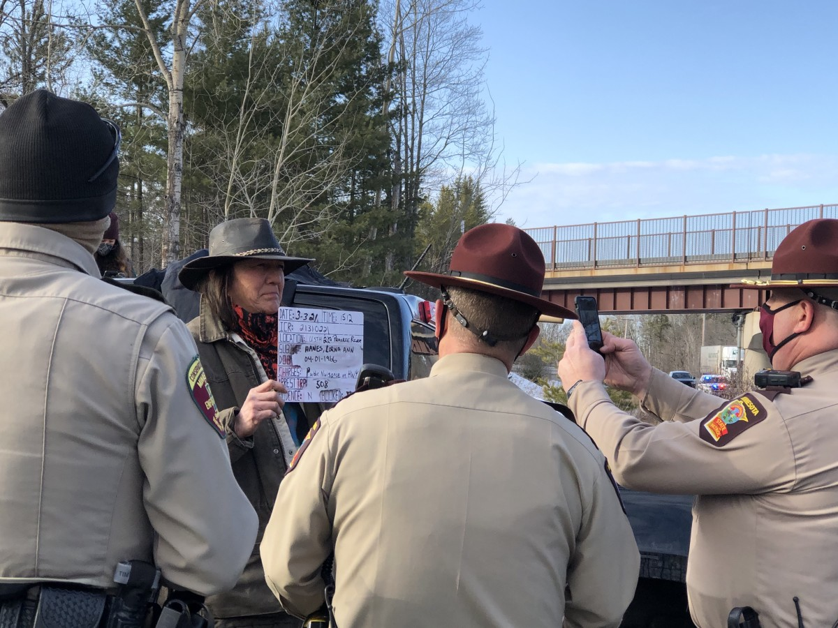 Officers stopped traffic on U.S. 2 to write and give citations to water protectors. The water protectors marched to observe the 30th anniversary of the 1991 spill into the Prairie River on March 3, 2021. (Photo by Mary Annette Pember, Indian Country Today)