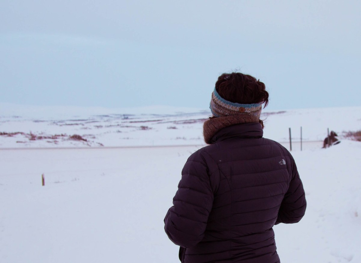 Resident of Nome, Lisa Ellanna, overlooking the snowy hills in Nome. (Photo by Brisa Alarcon, KNOM Radio)