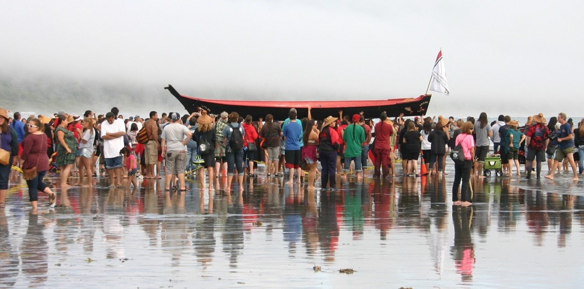 A canoe is carried ashore near the Quinault tribal village of Taholah during the 2013 Canoe Journey/Paddle To Quinault. The ocean is a central part of Quinault culture, but coastal areas are seeing stronger wave action and storm surges because of climate change. Quinault is making plans to move its community to higher ground. (Photo by Richard Arlin Walker/Indian Country Today)