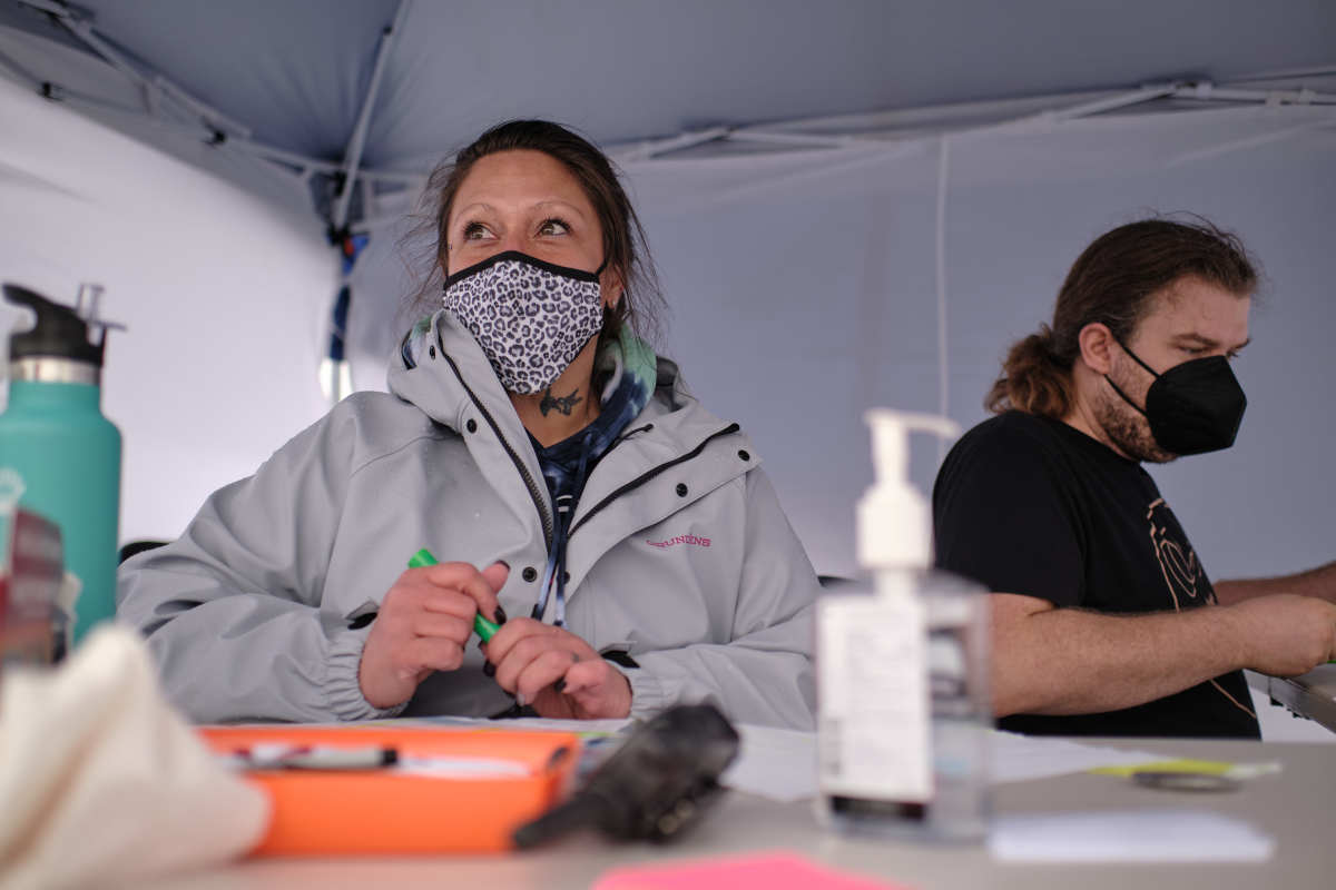Harm Reduction Outreach Specialist Sharon Bruns (left) and volunteer Alex Lane register people as they arrive at a temporary COVID-19 vaccine site organized by the Siletz Community Health Clinic for tribal members and their families in Salem. (Photo by Alex Milan Tracy for Underscore.news)