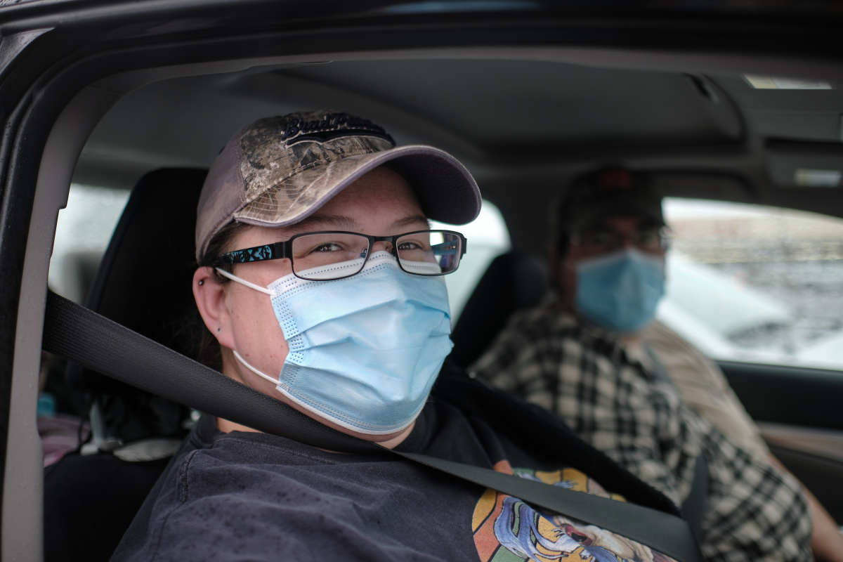 Crystal and Justin Tomlinson wait for any negative reactions after receiving their boosters at a temporary COVID-19 vaccine site organized by the Siletz Community Health Clinic for tribal members and their families in Salem. (Photo by Alex Milan Tracy for Underscore.news)